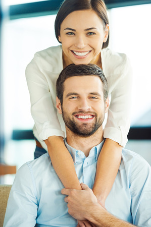 young couple smiling: Enjoying every moment together. Beautiful young loving couple bonding to each other and smiling