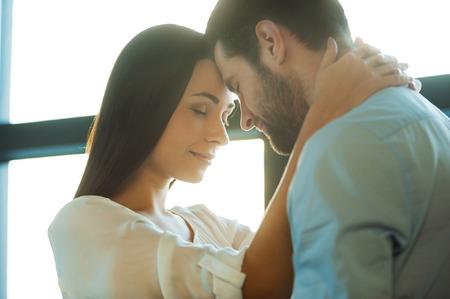 O amor está no ar. Bela jovem casal apaixonado, ligando um ao outro enquanto a mulher abraçando o namorado Foto de archivo