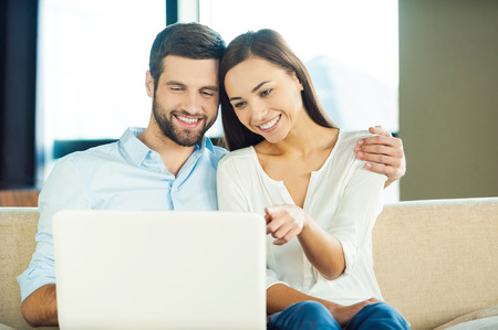 Surfing the net together. Beautiful young loving couple sitting together on the couch and looking at laptop Stok Fotoğraf - 34798991