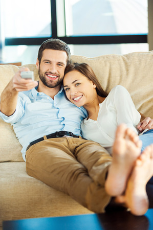 Watching TV together. Beautiful young loving couple sitting together on the couch and watching TV while man holding remote control and smiling
