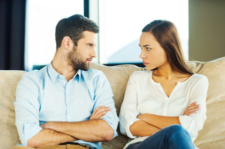 marido y mujer: Es tu culpa! Pareja joven enojado mirando el uno al otro y mantener los brazos cruzados mientras se est� sentado cerca uno del otro en el sof� Foto de archivo