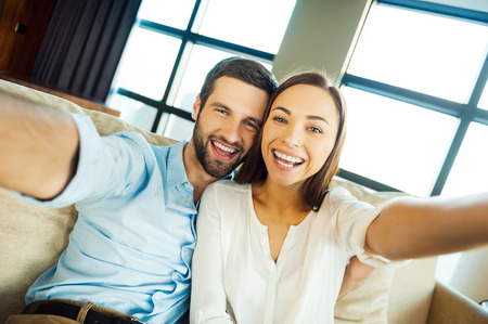photography themes: Capturing fun. Beautiful young loving couple bonding to each other and making selfie while sitting on the couch together Stock Photo