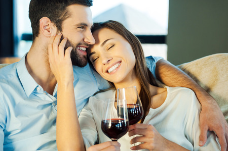 Love is a great feeling. Beautiful young loving couple sitting close to each other and drinking red wine Imagens