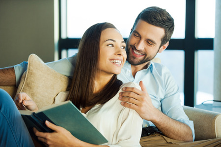 Spending great time together. Beautiful young loving couple bonding to each other and smiling while woman holding a book photo