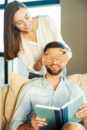 Guess who! Handsome young man holding book and smiling while woman covering his eyes with hands Stock Photo