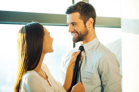 woman looking: Now you are ready! Beautiful young loving couple standing face to face and smiling while woman adjusting necktie of her husband