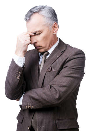 Too stressful day. Frustrated mature man in formalwear touching head with fingers and keeping eyes closed while standing against white background photo
