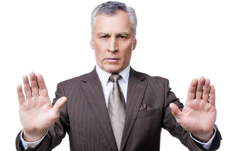 Stop it! Serious mature man in formalwear showing his palms and looking at camera while standing against white background