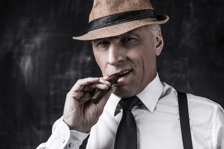 gangster background: Serious senior man in hat and suspenders smoking cigar and looking at you while standing against dark background