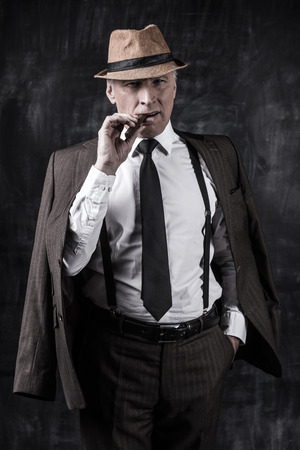 Serious senior man in hat and suspenders smoking cigar and looking at you while standing against dark background