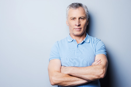 one senior man only: Portrait of confident senior man in T-shirt looking at camera and smiling while keeping arms crossed and standing against grey background Stock Photo