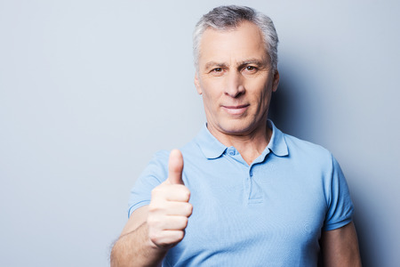 one senior man only: Cheerful senior man in casual showing his thumb up and smiling while standing against grey background