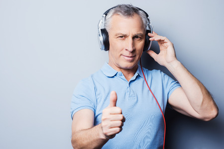 Portrait of senior man in headphones listening to music and showing his thumb up while standing against grey background photo