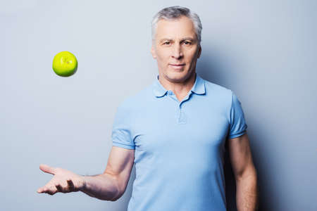 one senior man only: Confident senior man in casual throwing a green apple up and smiling while standing against grey background