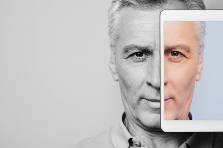 one senior man only: Live a colorful life. Black and white portrait of confident senior man with digital tablet covering half face