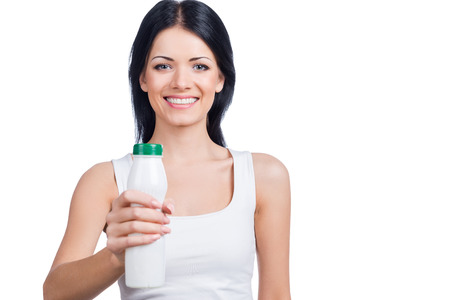 outstretching: Be healthy! Beautiful young smiling woman stretching out white bottle while standing against white background Stock Photo