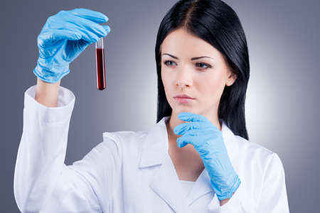 researches: Scientific researches. Female doctor in white uniform holding flask with blood while standing against grey background Stock Photo