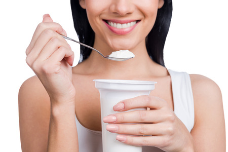 My special breakfast. Close-up of young smiling woman holding a spoon with sour cream while standing against white background