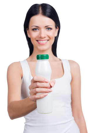 outstretching: Invigorating drink. Beautiful young smiling woman stretching out white bottle while standing against white background