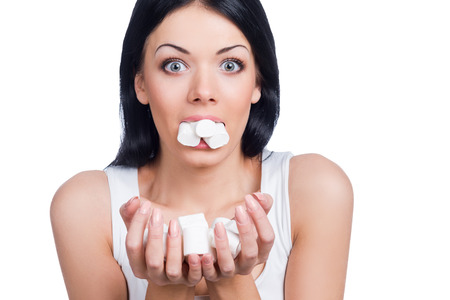 binge: Marshmallow paradise. Beautiful women holding marshmallow in her mouth and hands while standing against white background