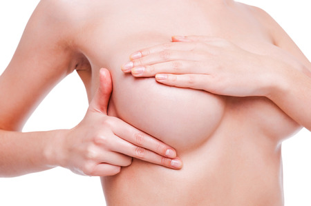 breast beauty: Examining breasts. Close-up of young shirtless woman examining her breasts while standing against  white background