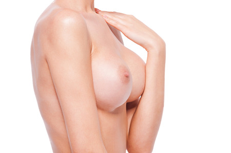 breast beauty: Perfect body. Close-up of beautiful young naked woman touching her shoulder while standing against white background