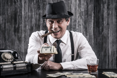 got: So we got a deal? Senior gangster in shirt and suspenders stretching out money and looking at you with smile while sitting at the table Stock Photo