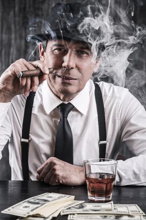 Mafia is niet slapen. Ernstige hogere mens in overhemd en bretels aan de tafel zitten en roken sigaar terwijl veel geld tot in de buurt hem