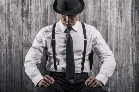 bossy: Hidden threat. Bossy senior man in gangster clothing sitting at the chair and against a wall Stock Photo