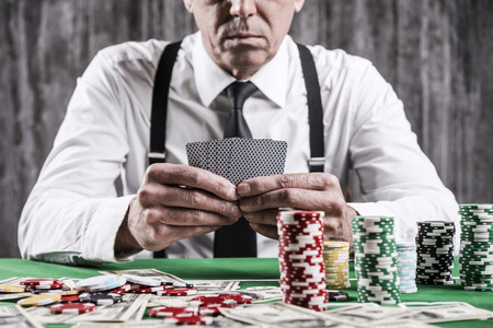 Poker player. Close-up of serious senior man in shirt and suspenders sitting at the poker table and holding cards  with money and  gambling chips laying all around him Stock Photo