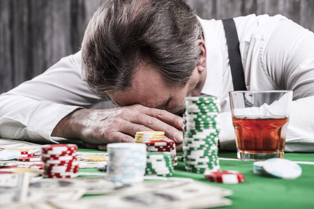 It is not my day. Depressed senior man in shirt and suspenders leaning his head at the poker table with money and gambling chips laying all around him Archivio Fotografico