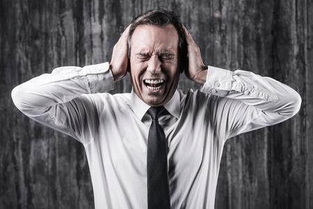 ojos cerrados: El estrés emocional. Estresado hombre maduro en camisa y corbata sosteniendo la cabeza en las manos y gritando mientras está de pie delante de la pared sucia