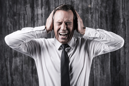 eye's closed: Emotional stress. Stressed mature man in shirt and tie holding head in hands and shouting while standing in front of dirty wall