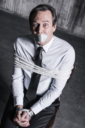 Feeling shocked and hopeless. Top view of tied up businessman with adhesive tape on his mouth looking up with shock