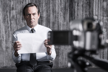 revenge: Hopeless hostage. Frustrated businessman caught by a criminal sitting in front of a dirty wall and holding paper while video camera filming it on the foreground