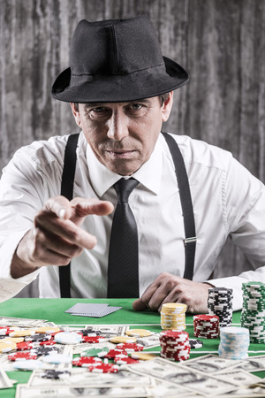 texas hold em: You own me money! Serious senior man in shirt and suspenders sitting at the poker table and pointing you while money and gambling chips laying all around him