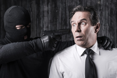 hijack: Victim of violence. Shocked businessman caught by a criminal aiming his head with gun Stock Photo