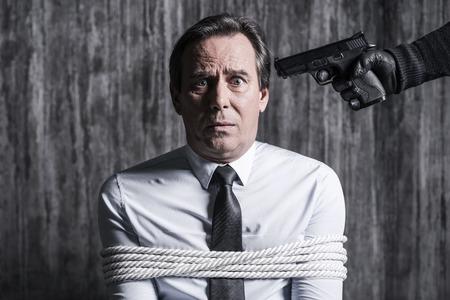ください !ビジネスマンによって銃で彼の頭を目指す犯罪者によってつかまえられる手が離せない