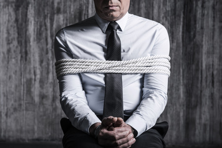 Fear and hopelessness. Cropped image of tied up businessman sitting at the chair with dirty wall  in the background Standard-Bild