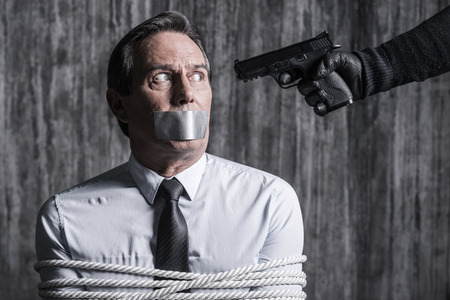 duct tape: Please no. Tied up businessman with adhesive tape on his mouth sitting in front of the dirty wall while someone aiming his head Stock Photo