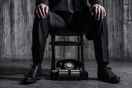 Waiting for important call. Close-up of bossy man in formalwear sitting at the chair with old-fashioned telephone laying near his feet