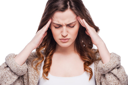 expressing negativity: Feeling headache. Frustrated young woman touching her head and expressing negativity while standing isolated on white