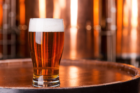 pub food: Fresh beer. Close-up of glass with beer standing on the wooden barrel with metal containers in the background Stock Photo