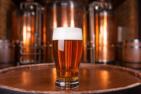 마을 최고의 맥주. 백그라운드에서 금속 용기와 나무 통에 신선한 맥주 서와 유리의 근접