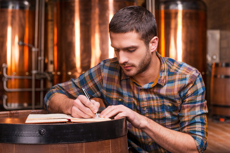 distillery: Planning his beer business. Confident young man in casual shirt writing something in his note pad while leaning at the wooden barrel with metal containers in the background