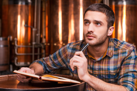 Generating ideas for his brewery. Thoughtful young man in casual shirt holding note pad and looking away while leaning at the wooden barrel with metal containers in the background