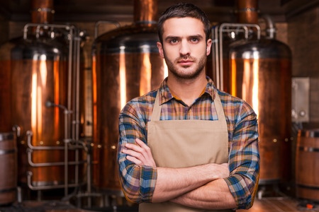 occupation: Confident brewer. Confident young male brewer in apron keeping arms crossed and looking at camera while standing in front of metal containers