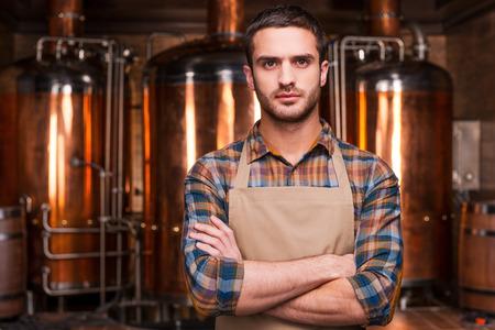 Przekonany piwowarskim. Przekonany, młody mężczyzna piwowarskim w fartuch trzymając rękami i patrząc na kamery, stojąc przed pojemników metalowych