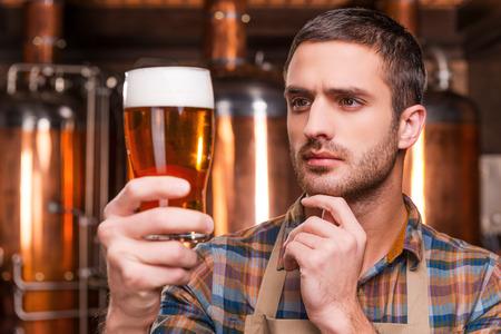 control de calidad: El control de calidad de la cerveza. Cervecero masculino joven pensativo en el delantal de la celebraci�n de vaso con cerveza y mirarlo mientras est� de pie delante de recipientes de metal