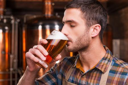 hombre tomando cerveza: Cata de cerveza recién hecho. Cervecero masculino joven hermoso en el delantal de la degustación de cerveza fresca y manteniendo los ojos cerrados mientras está de pie delante de recipientes de metal Foto de archivo